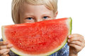 Close up of boy peeking over water melon shot a cute happy smiling a juicy slice watermelon isolated on white Stock Photography