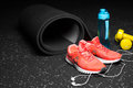 Close-up of bright training shoes, dumb-bells, rubber mat, blue bottle, and headphones on a black spotted background.