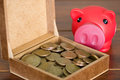 Close up brown box filled with dollar coins, pink piggy bank sitting next to it Royalty Free Stock Photo