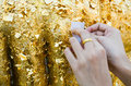 Close up buddhist s hand placing gold leaf buddha statue Royalty Free Stock Image