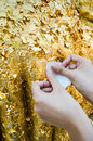 Close up buddhist s hand placing gold leaf buddha statue Royalty Free Stock Photos