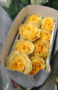 Close up of a bunch of yellow rose in crepe box under sun light Royalty Free Stock Photo