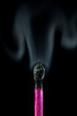 Close up burnt out match with smoke of a pink wooden a sulfur head isolated on a black background natural symbolizing Stock Image