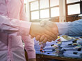Close up of business people shaking hands over documents stack Royalty Free Stock Photo