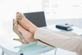 Close up of a businesswoman in high heels relaxing with feet up bright office Royalty Free Stock Image