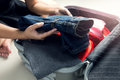 Close up of businesswoman packing clothes into travel bag Royalty Free Stock Photo
