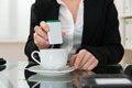 Close-up Of Businesswoman Putting Sugar In Cup Royalty Free Stock Photo