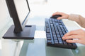 Close up on businesswoman typing on keyboard in bright office Royalty Free Stock Images