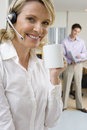 Close up of businesswoman wearing headset holding mug man in background smiling portrait men Stock Images