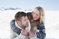 Close up of a cheerful couple holding hands on snow men and women covered landscape Royalty Free Stock Image