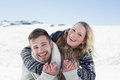 Close up of a cheerful couple holding hands on snow men and women covered landscape Royalty Free Stock Photography