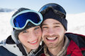 Close up of a cheerful couple with ski goggles on snow portrait covered landscape Royalty Free Stock Image