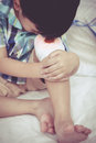 Close up child injured wound on the child s knee with bandage bed in bedroom bloody sad boy human health care and medicine Royalty Free Stock Photography
