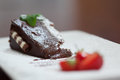 Close up of chocolate cake with strawberries on white plate Royalty Free Stock Photos