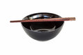 Close up chopsticks and black bowl isolated . Royalty Free Stock Photo