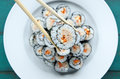 Close up of chopsticks holds sushi maki gunkan roll Royalty Free Stock Photo
