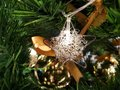 Close up christmas accessories hanging on decorated with lights Christmas tree. Royalty Free Stock Photo