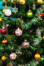 Close up of Christmas tree with ornaments  baubles, snowflakes, teddy bears, sleighs, gingerbread house, pine cones and lights. Royalty Free Stock Photo