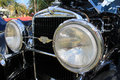 Close up classic car s stylish headlamps and grill headlamp on luxury american stutz ma sv with open hood in shallow depth of Stock Images