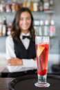 Close-up of cocktail glass in tray with waitress in background Royalty Free Stock Photo