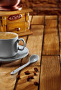 Close-up coffee cup and grinder on wooden table Royalty Free Stock Photo