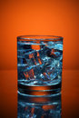 Close up of cold water glass with ice cubes.