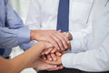 Close up on colleagues hands all together in bright office Stock Photography
