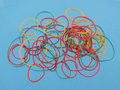 Close up of colourful rubber bands on a blue background. Royalty Free Stock Photo