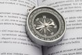 Close up of compass on book an opened indicating direction Stock Photos