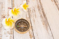 Close up compass and tropical plumeria flower on wooden table background Stock Photos