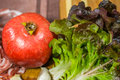 Close up composition of pomegranate, violet - green lettuce and garlic on a wooden board Royalty Free Stock Photo