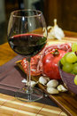 Close up composition of pomegranate, yellow muscat grape, salami, glass of red wine and garlic on a wooden board Royalty Free Stock Photo