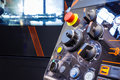 Close up of control panel of CNC machine with adjustment controls and push buttons. Selective focus.
