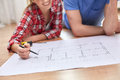 Close up of couple with blueprint at home repair building renovation and people concept happy looking Royalty Free Stock Photo