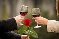 Close up of a couple drinking wine on valentines day romantic with rose in the mans hand Stock Photography