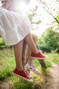 Close up of couple in keds sitting on bench. Royalty Free Stock Photo