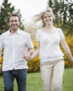 Close up of couple running through park holding hands Royalty Free Stock Photo