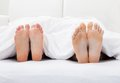 Close up of couple s feet sleeping on bed in bedroom Stock Image