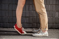 Close up of couple's legs in keds over grey wall. Royalty Free Stock Photo