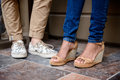 Close up of couple's legs in keds standing at street. Royalty Free Stock Photo