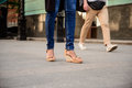 Close up of couple's legs in keds walking down street. Royalty Free Stock Photo