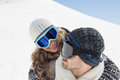 Close up of a couple in ski goggles against snow men and women covered hill Royalty Free Stock Image