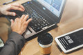 Close up cup of coffee on table. Businessman hands typing on his