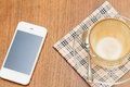 Close up a cup of coffee on wooden table and mobile phone Royalty Free Stock Image