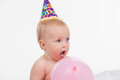 Close up of cut little baby with pink balloon standing in party hat isolated over white background Stock Images