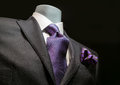 Close up of a dark gray jacket with striped purple tie and handkerchief on black background Stock Images