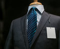 Close up of a dark gray striped jacket with striped blue tie and a blank white tag on the left lapel Stock Photos