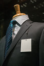 Close up of a dark gray striped jacket with striped blue tie and a blank white tag on the left lapel Stock Image