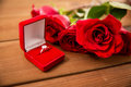 Close up of diamond engagement ring and red roses love proposal valentines day holidays concept gift box with on wood Stock Images