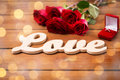 Close up of diamond ring, red roses and word love Royalty Free Stock Photo